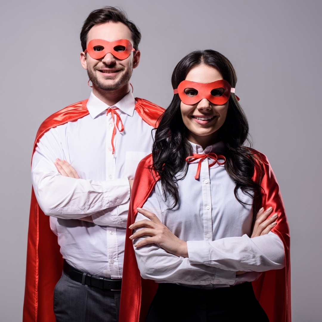 Man and woman in business clothing with superhero capes.