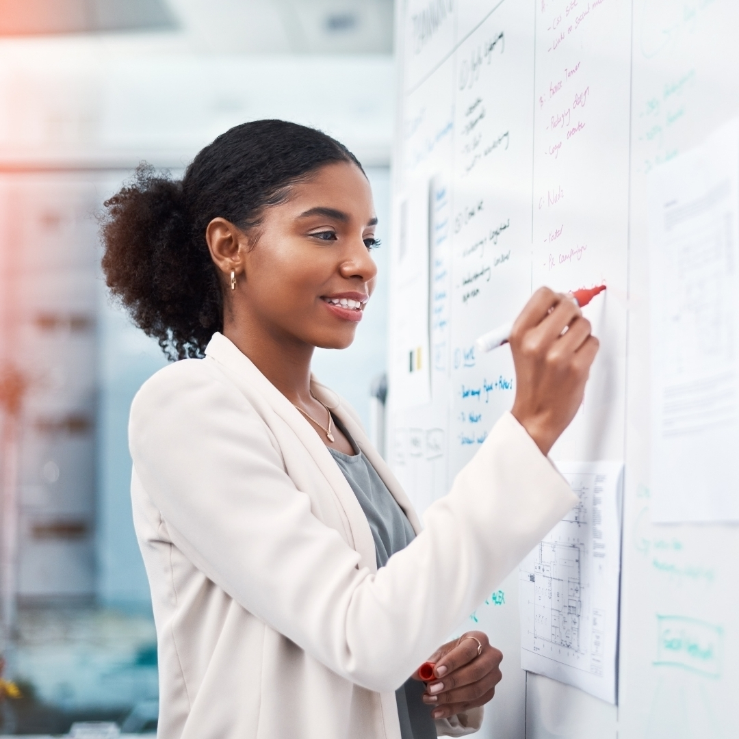 Young Black business woman working at a whiteboard.